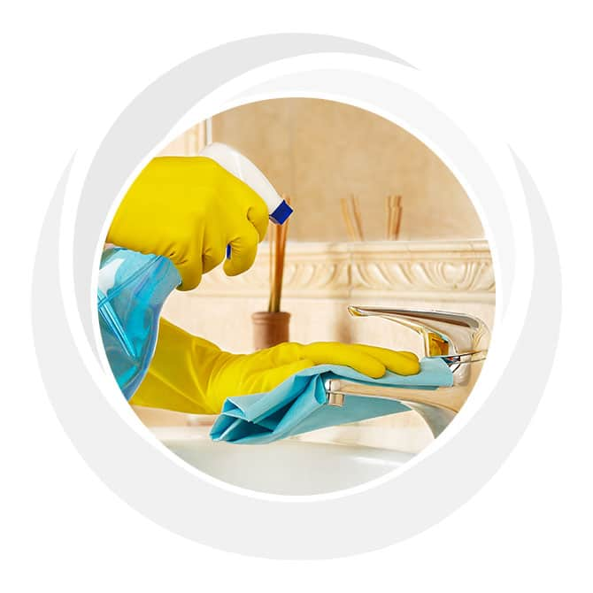 Hands in rubber gloves cleaning with a spray bottle.