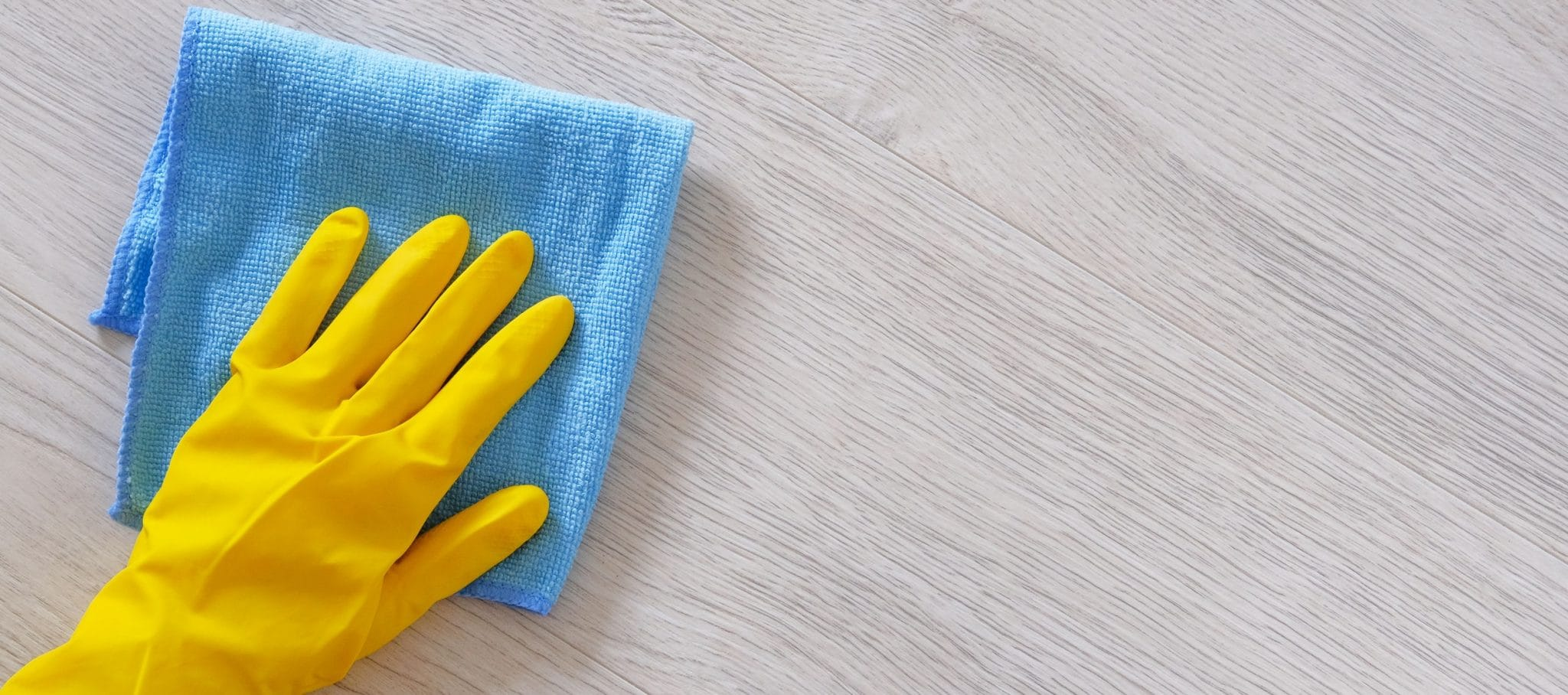 Hand in rubber protective glove with blue microfiber cloth is wiping floor