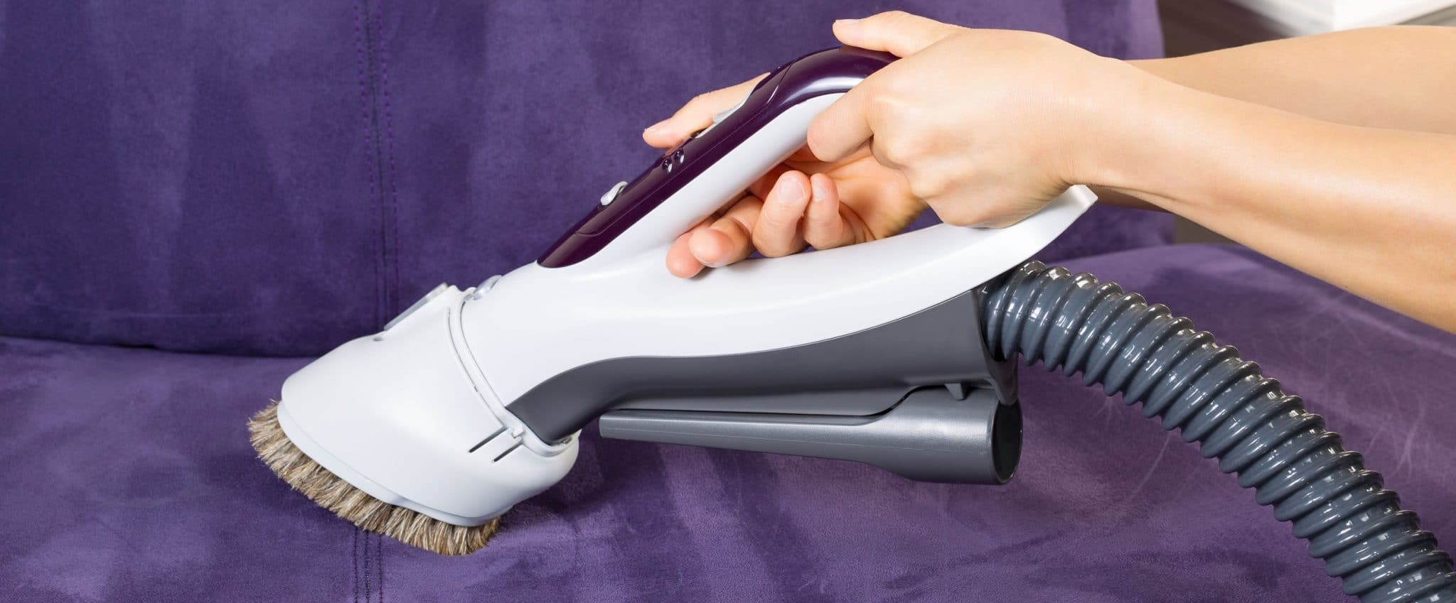 Female hands holding vacuum cleaner extension for cleaning suede leather couch